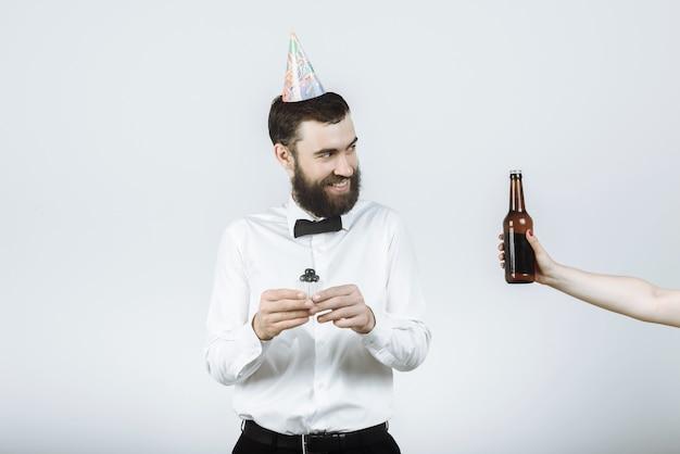 맥주를 들고 촛불과 손으로 케이크를 들고 파티 모자에 행복 수염 된 hipster 남자