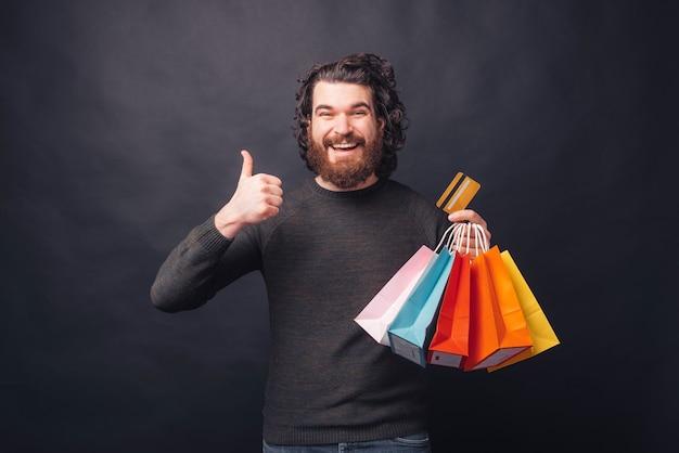 親指を立てて買い物袋とクレジットカードを持っている幸せなひげを生やしたヒップスターの男