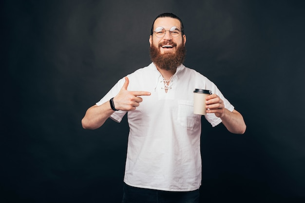 Happy bearded hipster man smiling and pointing at paper coffee cup to go