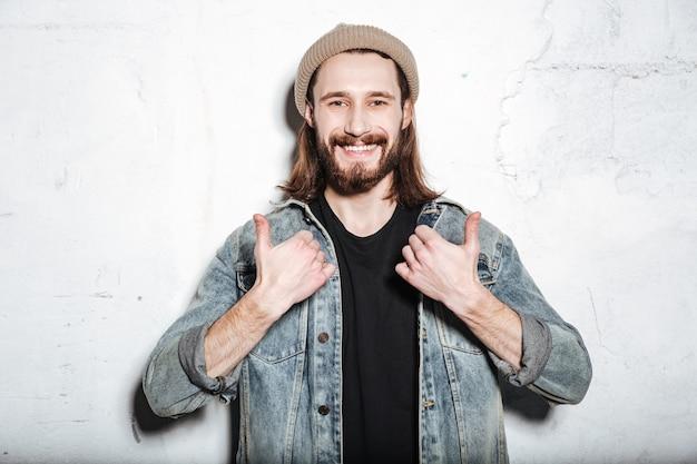 壁にポーズをとって親指を立てるジェスチャーをするジーンズのジャケットに身を包んだ帽子をかぶった幸せなひげを生やしたヒップスターの男