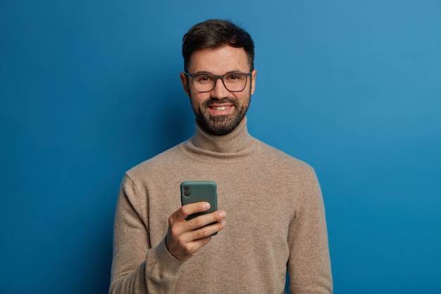 행복한 수염 난 남성 블로거가 블로그에 새로운 팔로워를 갖는 것을 기뻐합니다.