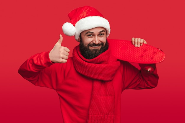 Happy bearded male in knitted scarf and santa hat