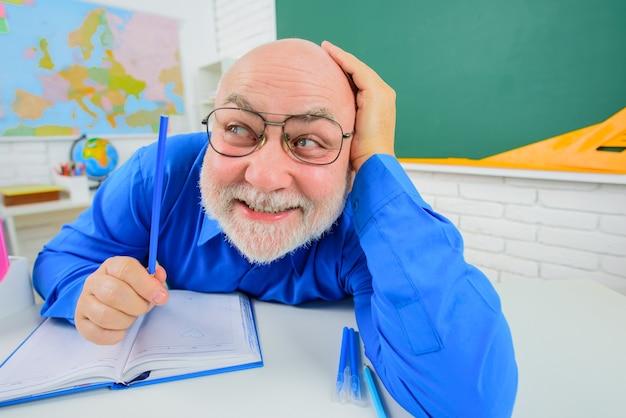 机の上の幸せなひげを生やした男性教師教室での試験の準備中の授業でひげを生やした男性教師