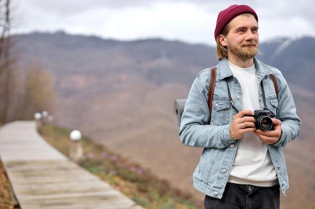 카메라가 걷고, 사진을 찍고, 웃고, 옆을 바라보는 행복한 수염 난 남성 관광객
