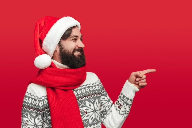 Happy bearded male in warm knitted sweater and santa hat