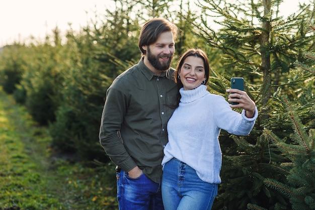 행복한 수염 난 남자와 그의 예쁜 여자 친구가 크리스마스 트리 농장에서 셀카 사진을 만들고 휴일을 준비합니다.
