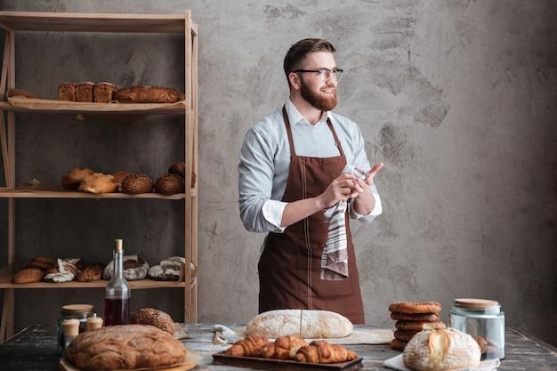 Счастливый бородатый мужчина пекарь, стоя возле много хлеба.