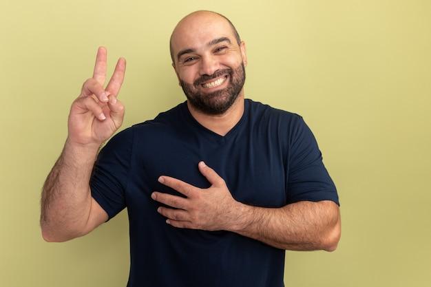 Felice uomo barbuto in maglietta nera che mostra v-segno tenendo la mano sul petto sorridendo allegramente in piedi sopra la parete verde