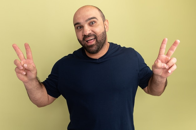Uomo barbuto felice in maglietta nera che sorride allegramente mostrando il segno di v in piedi sopra la parete verde