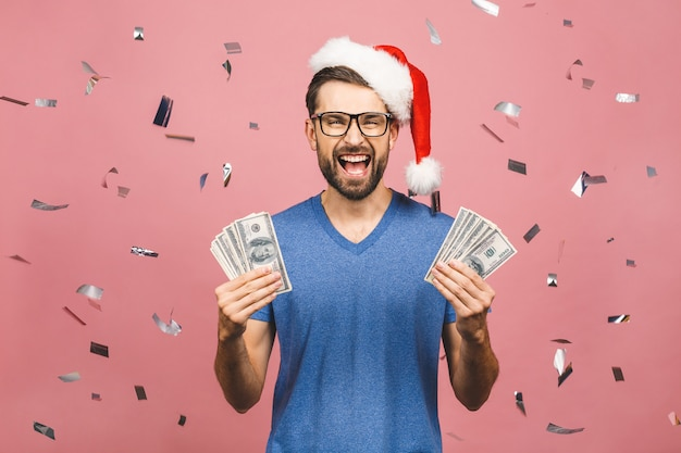 Happy bearded man in casual and christmas hat holding money