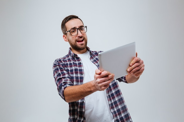 Happy bearded man in eyeglases playing on tablet computer