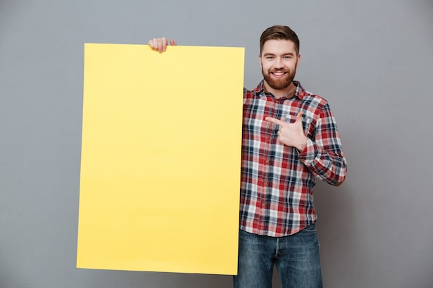 Happy bearded man holding blank board and pointing