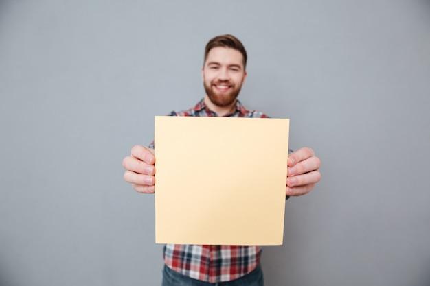 Uomo barbuto felice che tiene carta in bianco