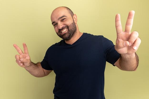 녹색 벽 위에 v 기호 서를 유쾌하게 보여주는 웃 고 검은 티셔츠에 행복 한 수염 난된 남자