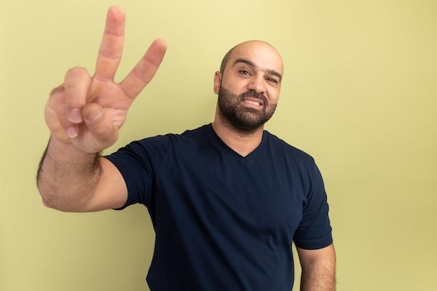 緑の壁の上に立っているvサインを示す自信を持って笑顔の黒いtシャツの幸せなひげを生やした男