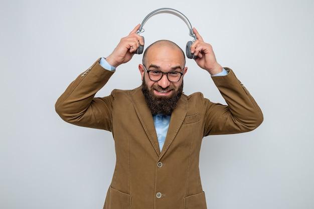 머리 위로 헤드폰을 끼고 안경을 쓰고 즐겁게 웃고 있는 갈색 양복을 입은 수염 난 남자