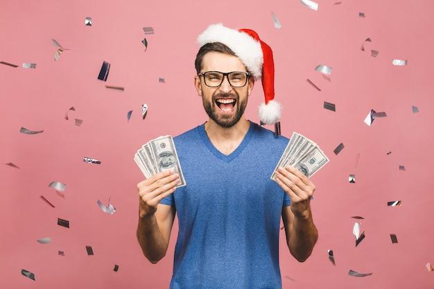 お金を保持しているカジュアルなクリスマス帽子で幸せなひげを生やした男