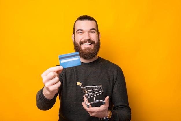Счастливый бородатый мужчина в непринужденной обстановке стоит над желтой стеной, показывая кредитную карту и держа тележку для покупок