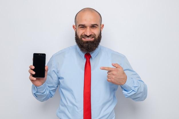 빨간 넥타이와 파란 셔츠를 입은 행복한 수염 난 남자는 흰색 배경 위에 밝게 서서 카메라를 바라보며 검지 손가락으로 스마트폰을 가리키는 스마트폰을 보여줍니다.