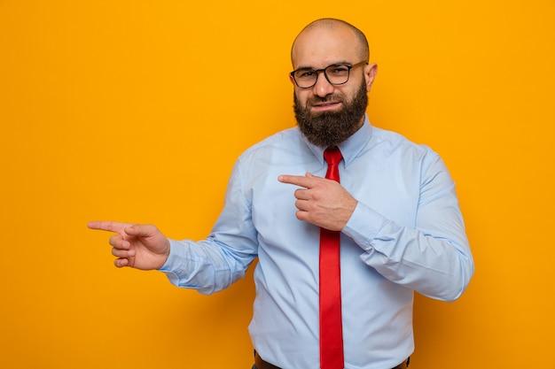 赤いネクタイとシャツを着た幸せなひげを生やした男は、オレンジ色の背景の上に立っている側に人差し指で自信を持って指しているカメラの笑顔を見て眼鏡をかけています