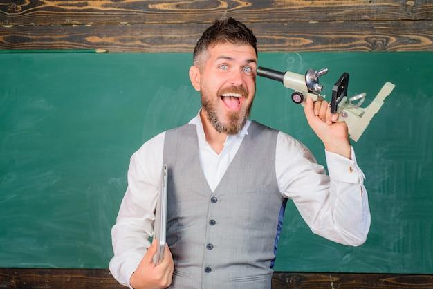科学の授業で幸せなひげを生やした男。 eラーニング、テクノロジー。科学、研究の概念。生物学または化学科学。学校に戻る。ノートパソコンと顕微鏡を持った前向きな先生。大学生。