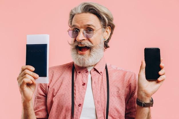 Счастливый бородатый человек в темных очках держит мобильный телефон и паспорт с билетами на розовом