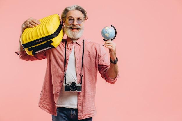 카메라와 함께 선글라스에 행복 한 수염 된 남자 가방과 지구본을 보유 하 고 핑크 여행을 준비합니다.