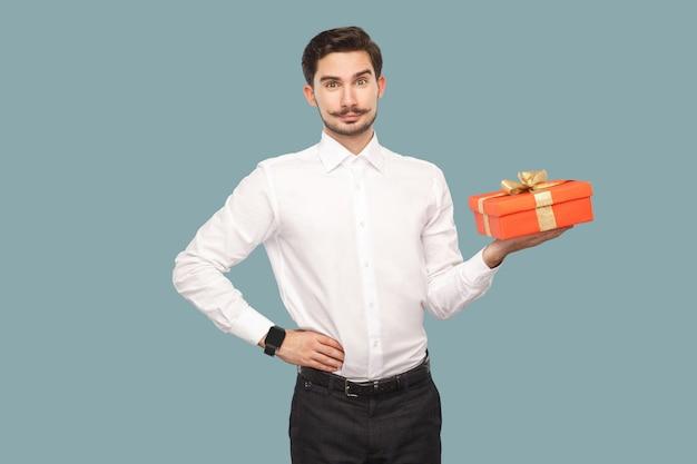 Счастливый бородатый мужчина в белой рубашке, стоя с рукой на талии, держа красную подарочную коробку, глядя в камеру с довольным лицом и улыбаясь. крытый, студийный снимок, изолированные на светло-синем фоне