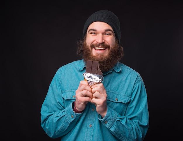 幸せなひげを生やした男は、カメラに微笑んでチョコレートバーを保持しています。