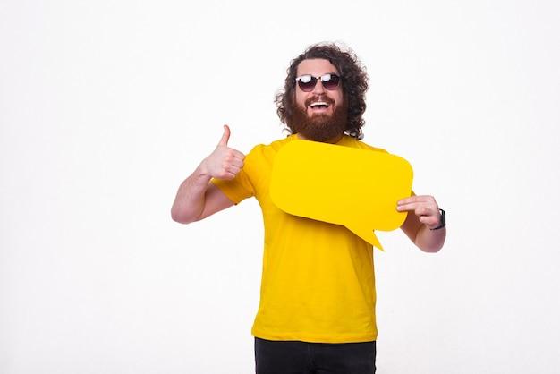 Счастливый бородатый мужчина держит речь желтого пузыря и показывает палец вверх.