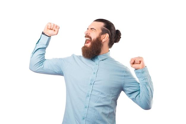 수염을 기른 행복한 남자가 승자 제스처를 하고 쾌활하게 비명을 지르고 있다.