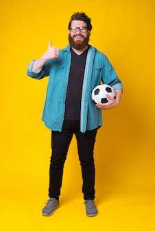 幸せなひげを生やした男がサッカーボールを押しながらジェスチャーを親指のように見せている