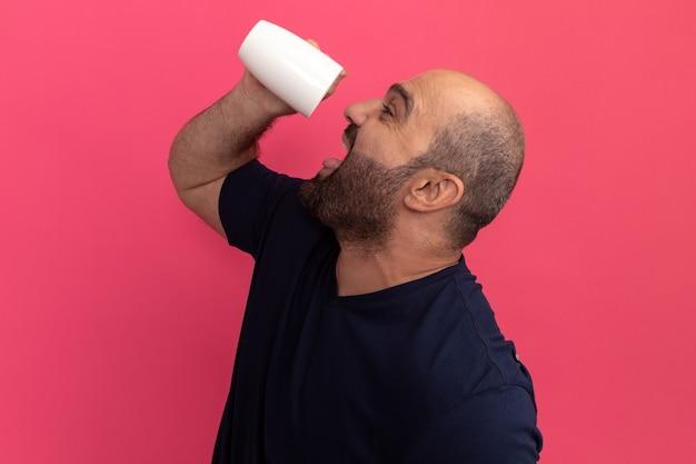 Uomo barbuto felice in maglietta blu scuro che tiene una tazza di tè andando a bere in piedi sopra il muro rosa