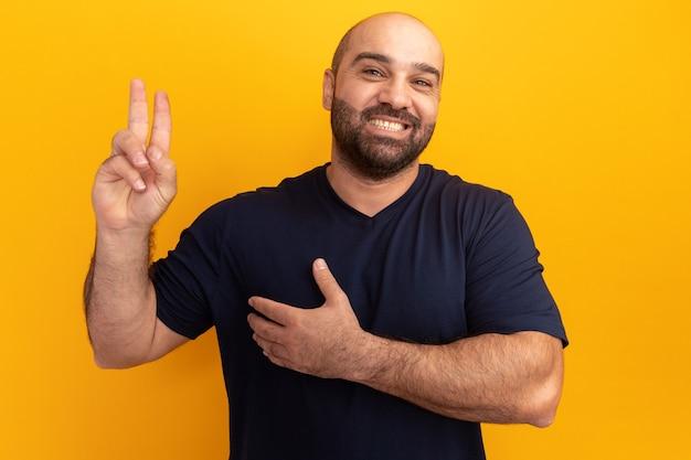 Uomo barbuto felice in maglietta blu scuro che tiene la mano sul petto che mostra le dita facendo una promessa in piedi sopra il muro arancione