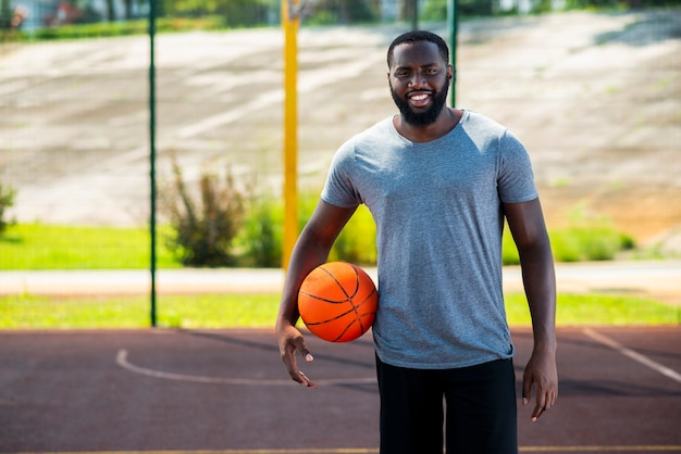 Счастливый бородатый человек на баскетбольной площадке