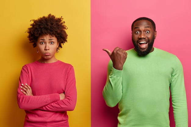 Happy bearded man points thumb on sad disappointed woman who feels offended and insulted, disagrees with someones opinion. ethnic couple expess different emotions, pose indoor over two colored wall
