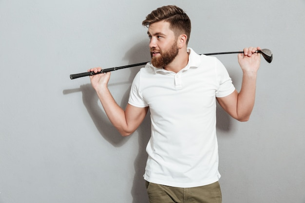 Happy bearded man posing with club and looking away