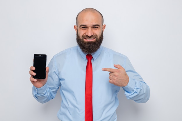 Happy bearded man in red tie and blue shirt showing smartphone pointing with index finger looking at camera smiling cheerfully standing over white background