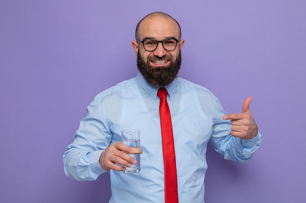 Happy bearded man in red tie and blue shirt wearing glasses holding glass of water pointing with index finger at it looking at camera smiling cheerfully standing over purple background