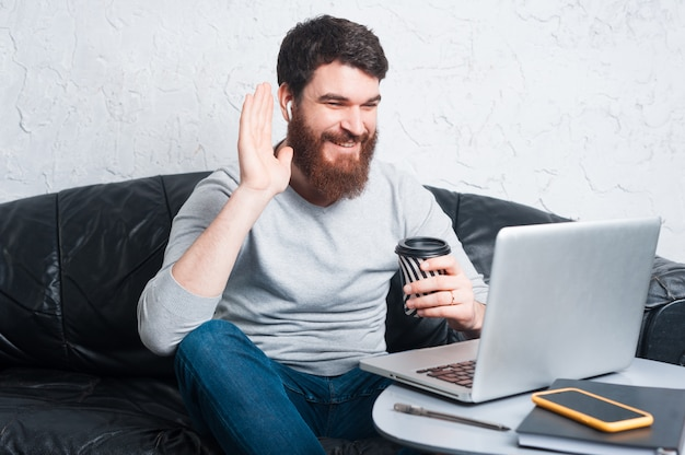 Happy bearded man saying hello, young man talking with someone and looking on laptop