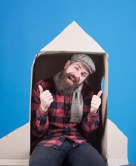 Happy bearded man sit in cardboard rocket adventure concept smiling man flying to space in rocket