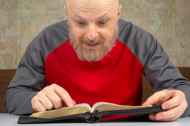 Happy bearded man studies the bible
