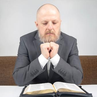 행복한 수염 난 남자는 성경을 연구합니다. 종교와 기독교.
