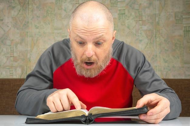 행복한 수염 난 남자는 성경을 연구합니다. 종교와 기독교