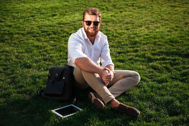 Happy bearded man in sunglasses and business clothes sitting on grass outdoors with backpack and tablet computer while looking at the camera