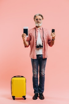 Happy bearded man in sunglasses holding a mobile phone and a passport with tickets on pink