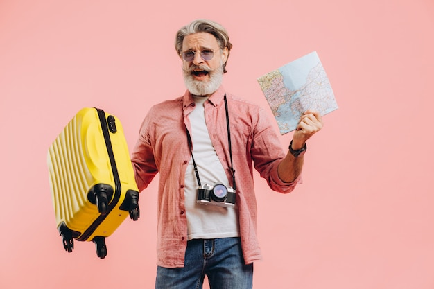 Happy bearded man in sunglasses holds a suitcase and a map, sings and dances