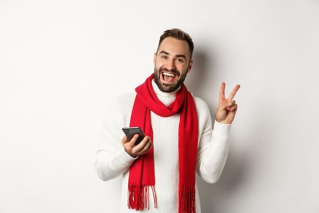 Uomo barbuto felice che utilizza smartphone, posa per una foto con segno di pace, in piedi in maglione invernale e sciarpa rossa, sfondo bianco.