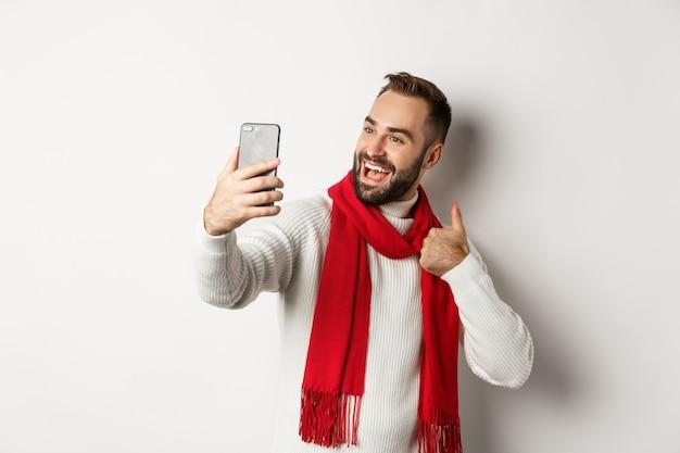 Videochiamata uomo barbuto felice e mostrando i pollici in su al telefono cellulare, come un regalo di natale, parlando online, in piedi su sfondo bianco