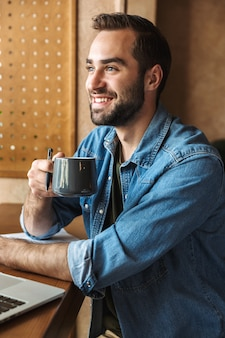Happy bearded man wearing denim shirt drinking coffee while working in cafe indoors